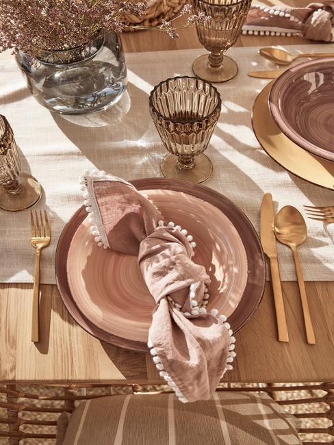 Serviesset in roze kleur met goudkleurige bestekset