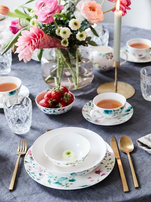 Serviesset in wit op grijs tafelkleed, transparante glazen vaas met bloemen