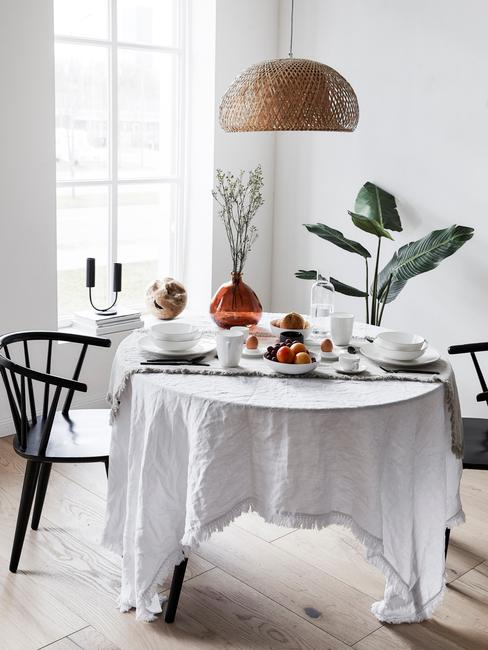 Eethoek in wit met wit tafelkleed en planten als decoratie
