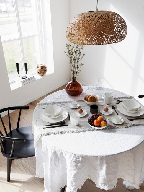 Eethoek in wit met wit tafelkleed en planten als decoratie en rotan hanglamp