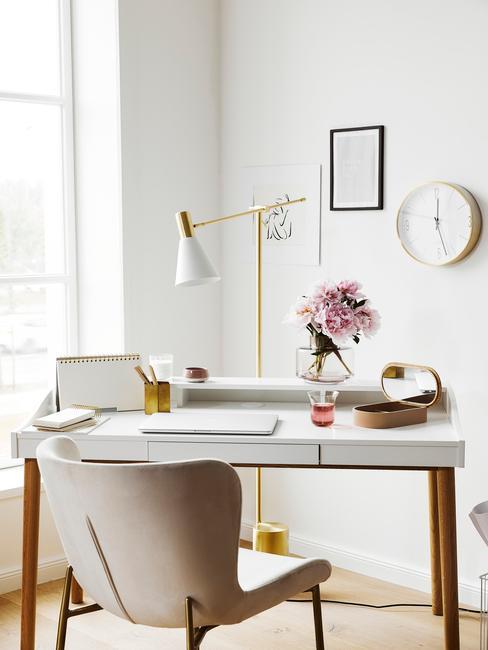 Groot houten bureau met comfortabele stoel naast het raam
