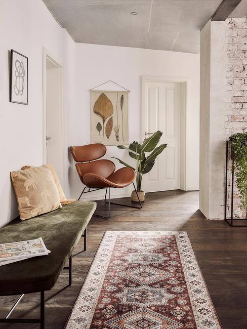 Leren fauteuil naast een planten en vloerkleed in vintage stijl