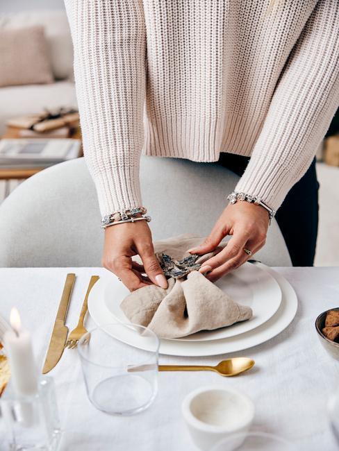 kerstservetten vouwen: gedekte tafel met kerstdecoratie en goudkleurige serviesse