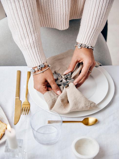 Beige servetten op wit tafel naast goudkleurige serviesset