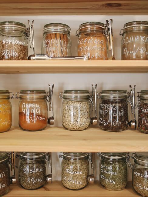 Kruiden opbergen in transparante potten op houten planken
