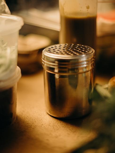 Metalen zoutvaatje op een houten tafel