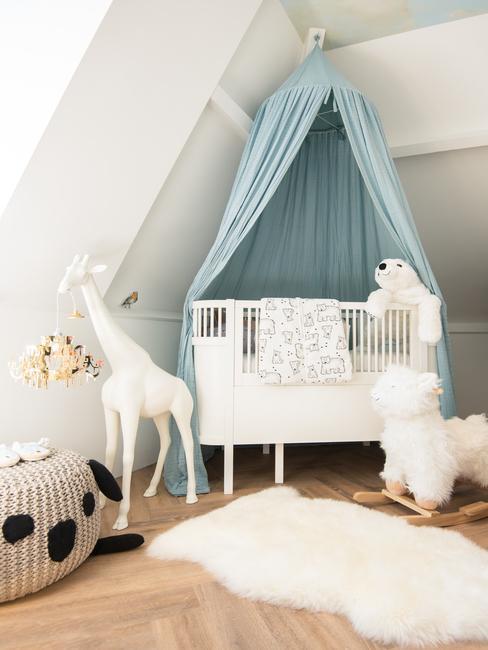 wit babybed met een blauw hemelvanger en aaibaar kleed