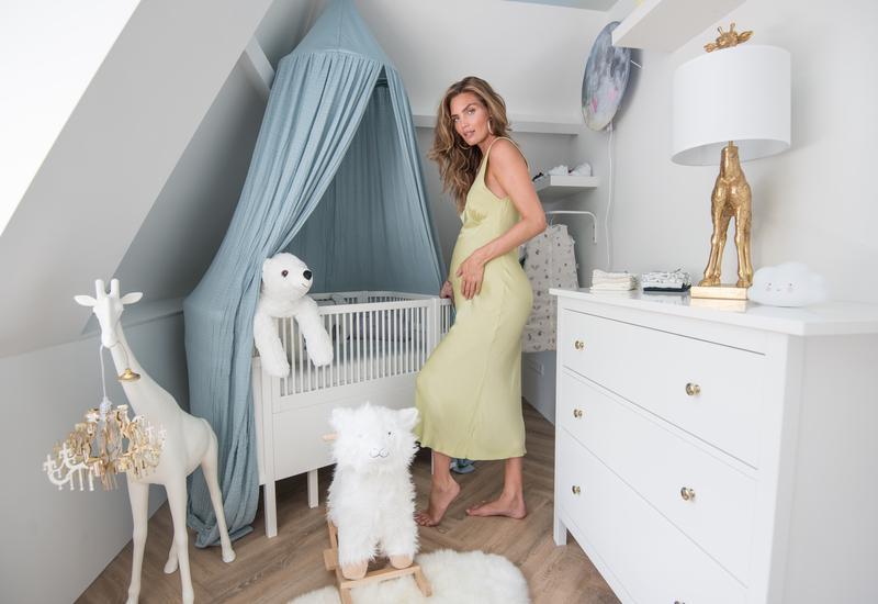 zwangere vrouw in een groene jurk bij een wit babybed