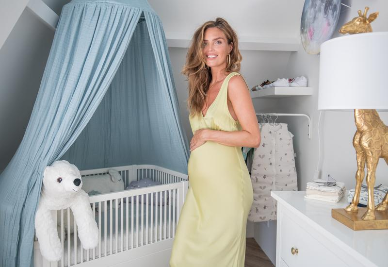 zwangere vrouw in een groene jurk voor een babybed