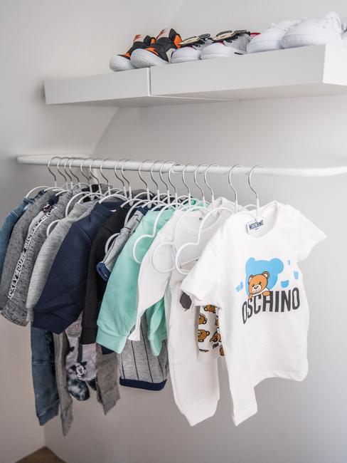 Babykleren op een witte stang aan witte kledinghangers