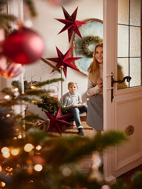Het meisje kijkt de kamer met de kerstboom in