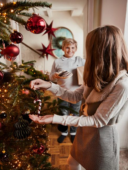 Een meisje dat een kerstboom in de woonkamer versiert