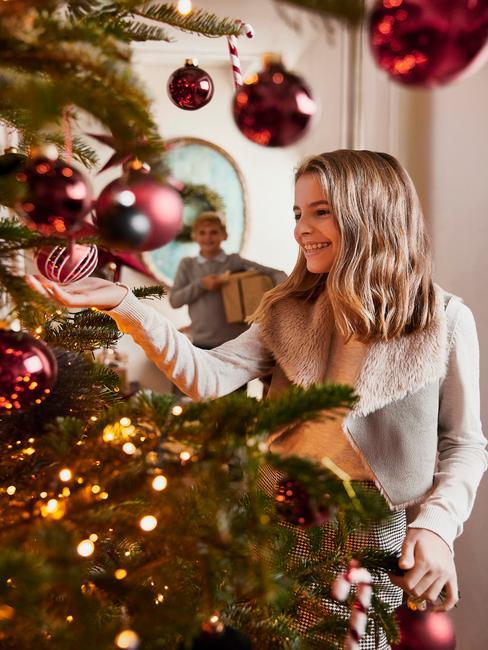 Het meisje versiert de kerstboom met rode kerstballen