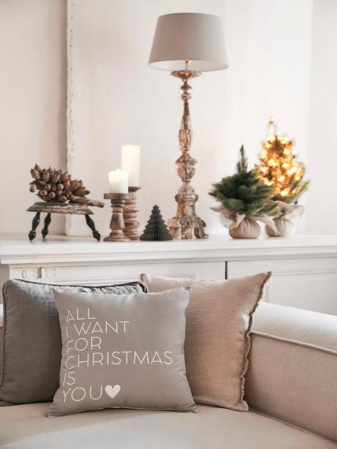 Woonkamer in wit en beige, gedecoreerd met kunstmatige kerstboom en verlichting op een witte ladekast