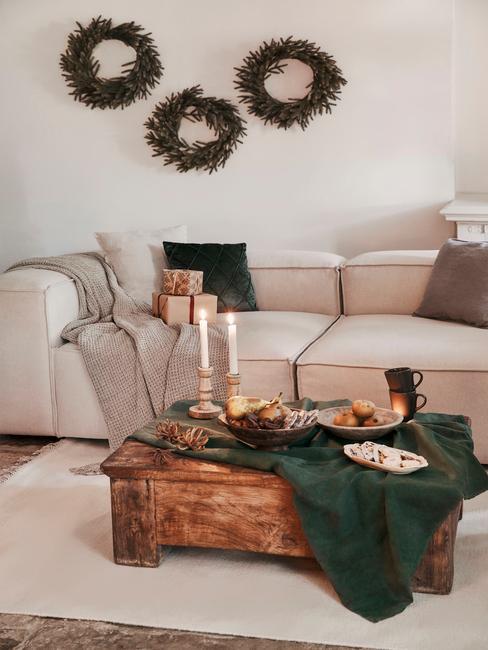 Comfortabele beige bank met sierkussens naast een houten salontafel met kaarsen