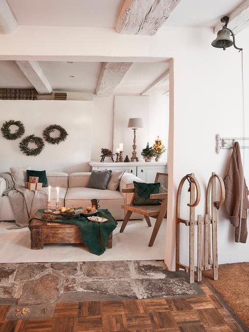 Kerstfilms: woonkamer met comfortabele beige bank met sierkussens naast een houten salontafel met kaarsen
