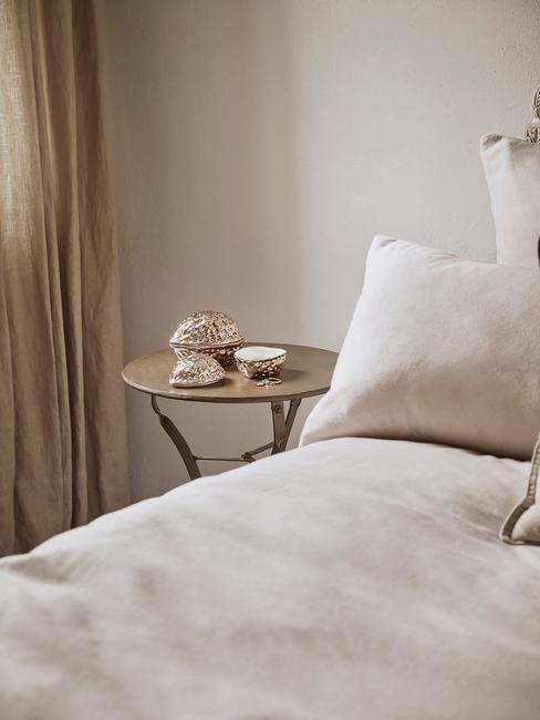 Een beige slaapkamer met wit beddengoed en houten nachtkastje