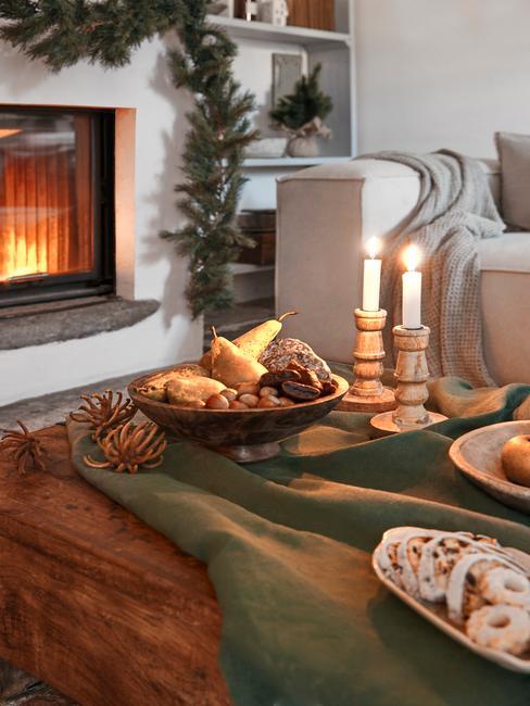 Kerstversiering boven de open haard naast een houten salontafel met kaarsen