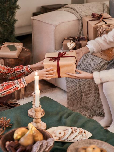 kerstbingo: moeder geeft haar zoon een cadeau aan een houten tafel met groene tafelloper