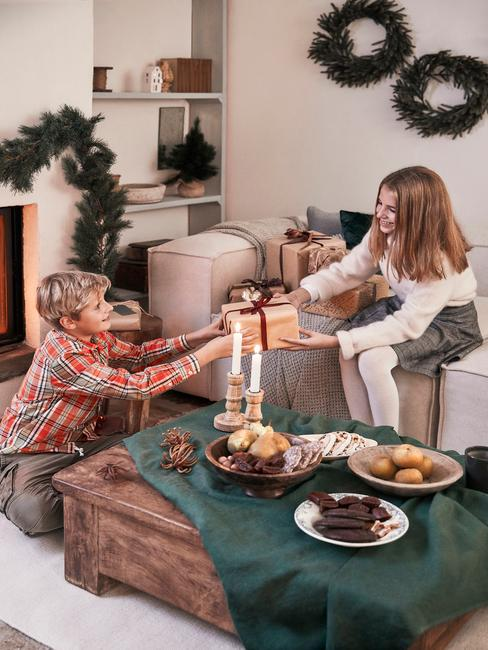 Moeder geeft haar zoon een cadeau aan een houten tafel met groene tafelloper