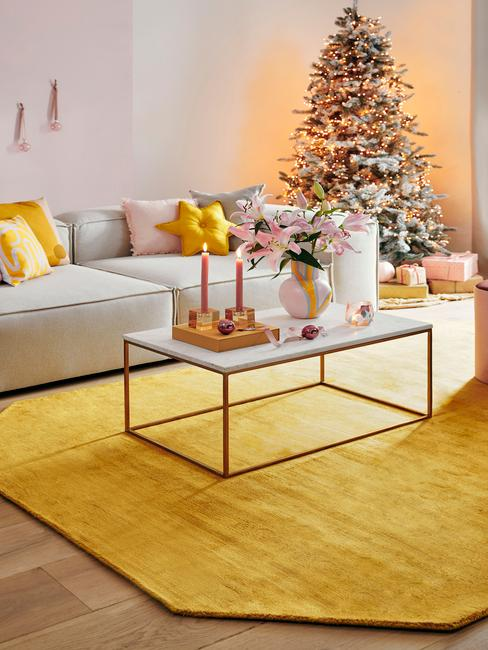 kerstbingo: woonkamer in het wit met een comfortabele bank en sierkussens en een witte salontafel met kaarsen en kerstversiering