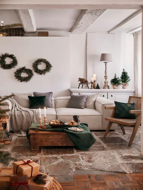 Woonkamer in het wit met een comfortabele witte bank en sierkussens en houten salontafel met kaarsen en kerstversiering