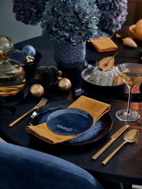 Adventskalender: gedekte tafel in blauw en goud kleur met kaarsen en gele servetten