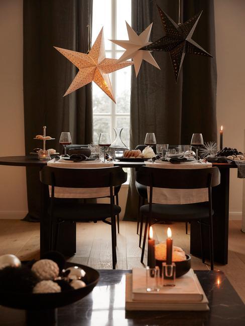 Adventskalender: Kerstdecoratie in een beige woonkamer met zwarte stoelen en een zwarte tafel