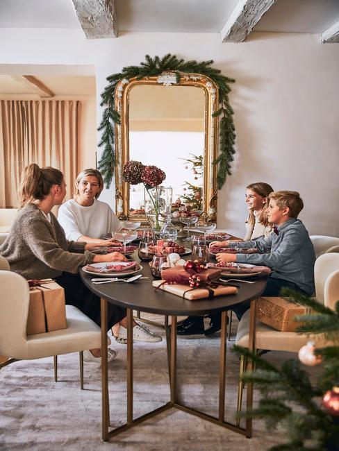 Familie zit aan een grote tafel achter een enorme spiegel met krans