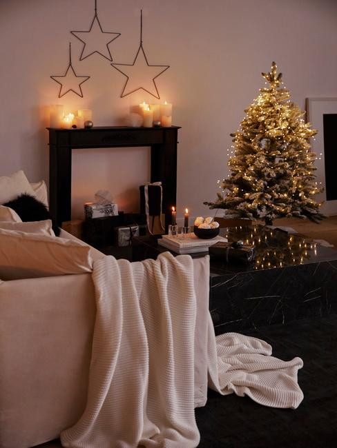 Kerstcadeau man: Woonkamer in het wit met kerstversiering en een comfortabele bank met een witte deken