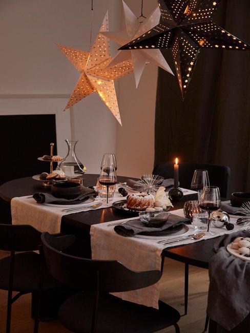 Kerstdecoraties boven de gedekte tafel met een witte tafelloper, bestekset in zilver, zwarte serviesset en grijze servetten