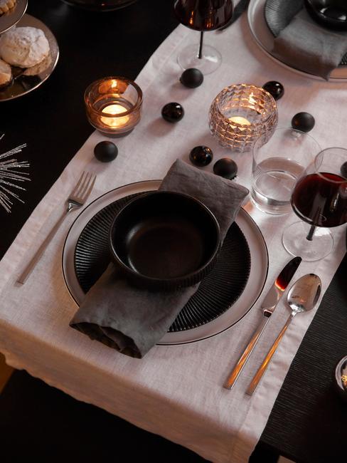 Kerstcadeau man: zwarte eettafel met witte tafelloper, bestekset in zilver, zwarte serviesset en grijze servetten