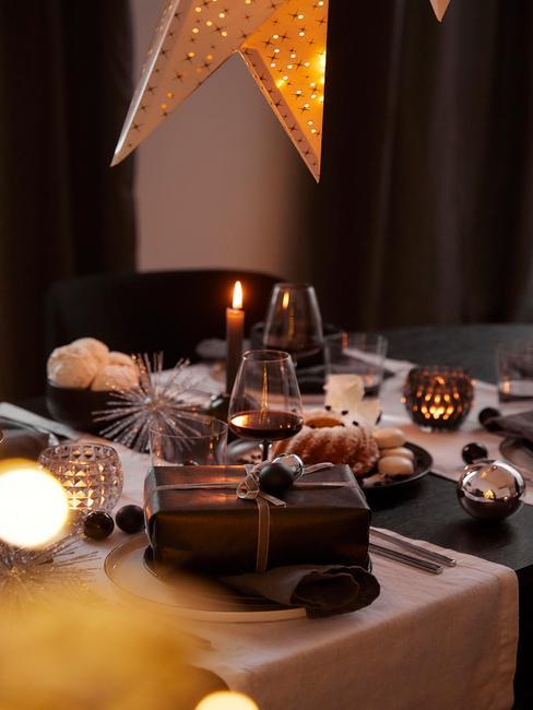 Gedekte tafel met een witte tafelloper, bestekset in zilver, zwarte serviesset en grijze servetten