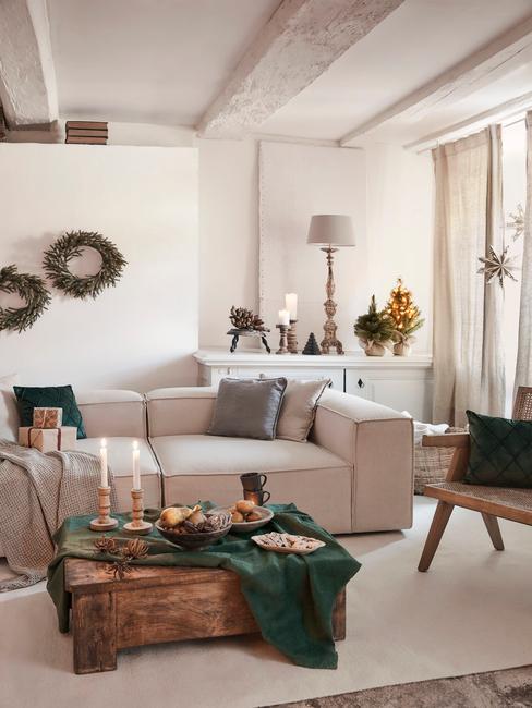 Woonkamer in wit met kerstversiering en comfortabele zitbank naast een houten salontafel met een groen tafelkleed en kaarsen