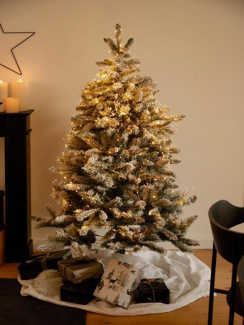 Kerstboom met gouden bommen en lampjes in de kamer