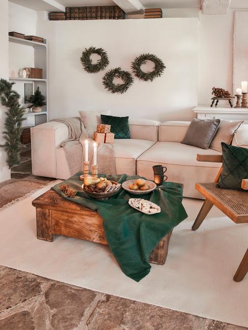 Kerstcadeau vrouw: comfortabele zitbank met sierkussens met houten salontafel en groene tafelloper
