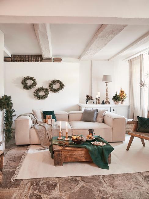 Woonkamer in wit met kerstversiering en een houten salontafel met een groen tafelkleed en kaarsen
