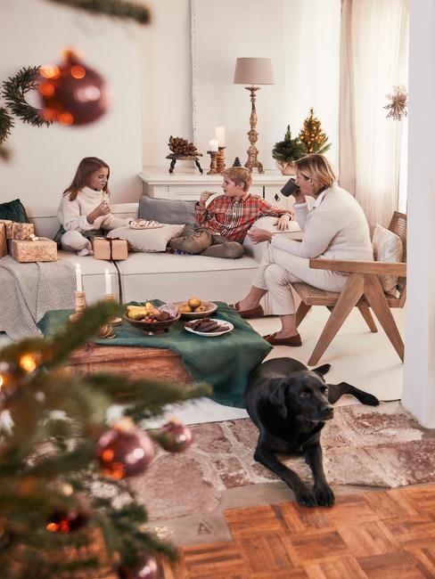 Kerstcadeau vrouw: vrouw zittend op de rotan stoel in de witte woonkamer