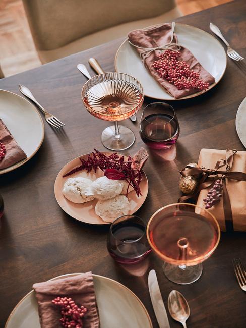 Kerstcadeau vrouw: gedekte tafel met bestekset in zilver en roze servetten