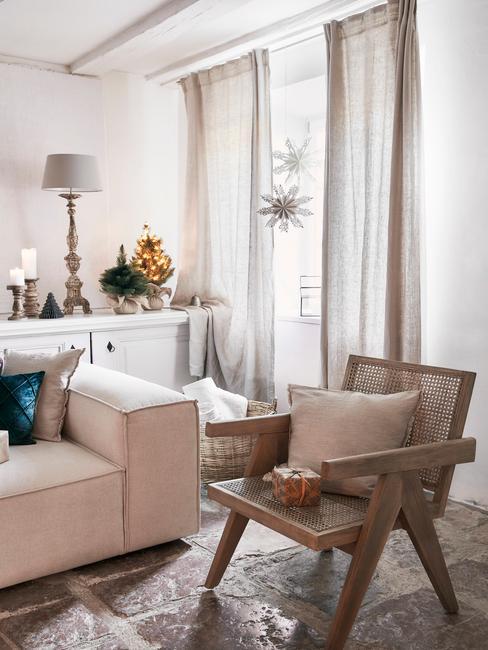 Woonkamer in wit met met beige zitbank en rotan stoel met sierkussen