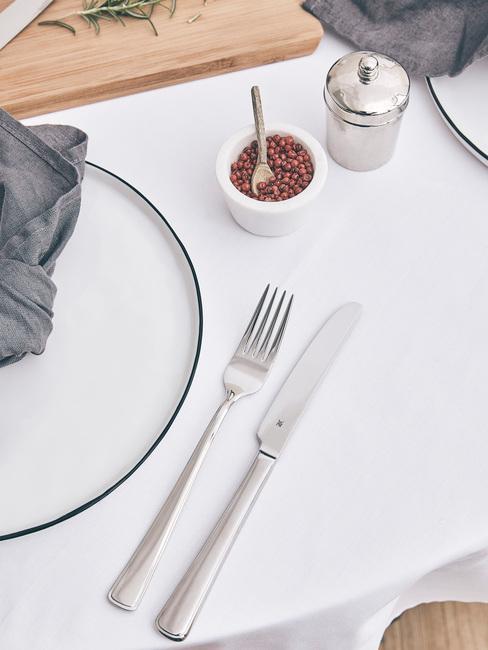 Gedekte tafel in scandi stijl met wit tafelkleed en witte serviesset met bestekst in zilver kleur