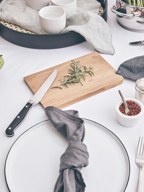 Gedekte tafel met wit tafelkleed en witte serviesset met bestekst in zilver kleur naast een houten snijplank