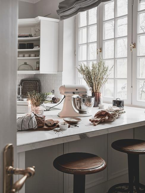 Keuken in wit met kookaccessoires op het blad en houten barkrukken