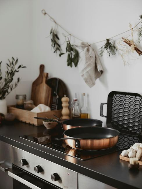 Keuken in cottage stijl met pannen in roestbruin en houten snijplank