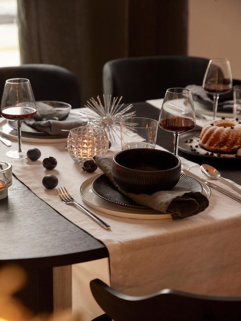 Gedekte tafel met serviesset in zwart, witte tafelloper en kerstdecoratie
