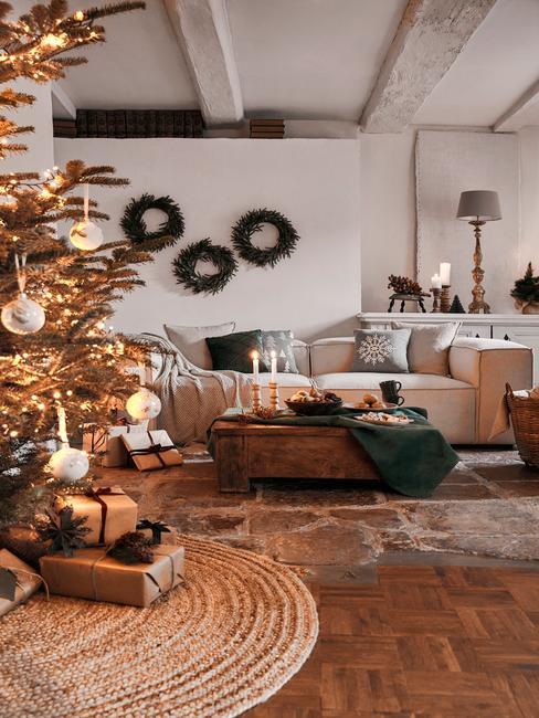 Comfortabele beige bank met sierkussens naast een houten salontafel met kaarsen en grote kerstboom