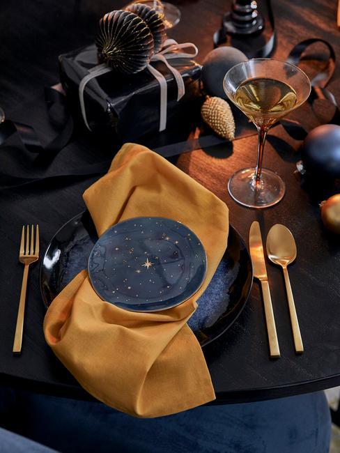 Gedekte tafel met serviesset en besteksset in goud kleur en gele servetten
