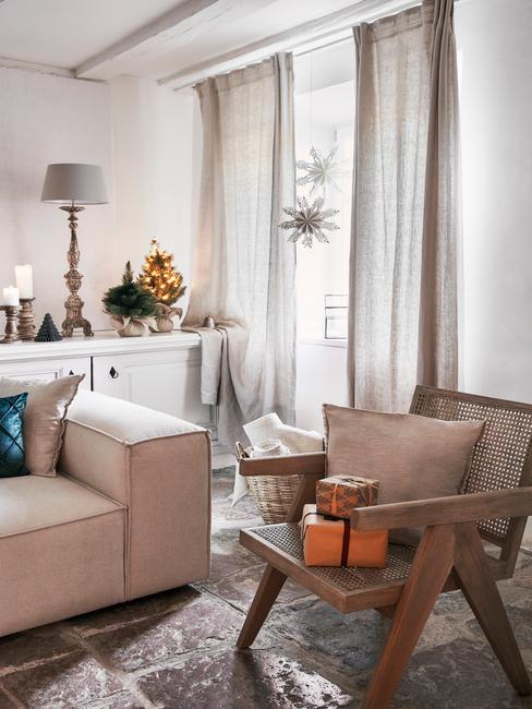 Woonkamer in wit met comfortabele zitbank naast een rotan fauteuil