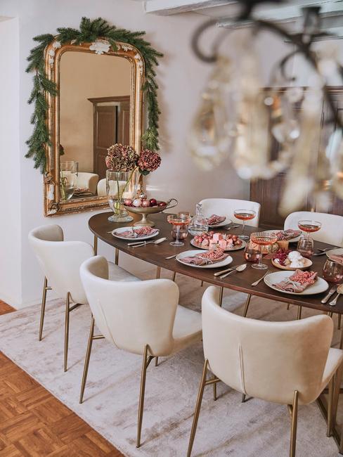 Fluwelen stoelen en gedekte tafel met porseleinen serviesset en kerstdecoratie