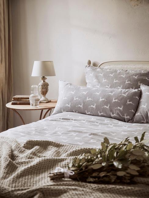 Slaapkamer in wit met grijs beddengoed en houten bijzettafel met tafellamp
